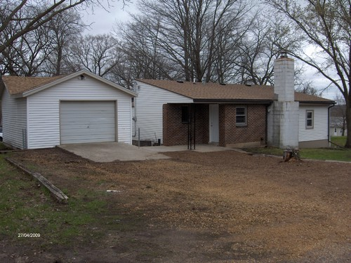back of house oversized single garage with opener.  covered patio.