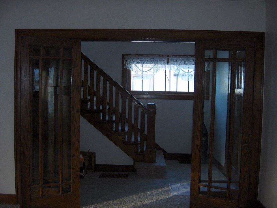 french doors from formal room to the open stairway.